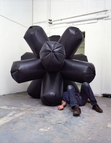 Man lying under inflatable sculpture