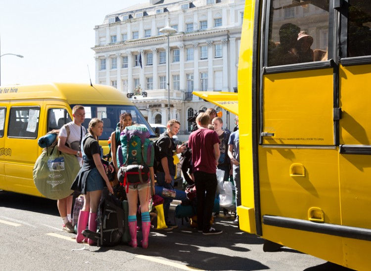 Group of young people wait to board the big yellow bus